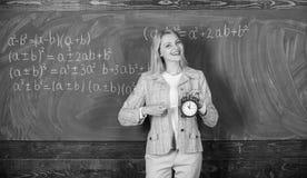 Sveglia della tenuta dell'insegnante della donna Si preoccupa per disciplina Tempo di studiare Anno scolastico benvenuto dell'ins immagini stock