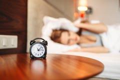Sveglia, donna che copre le sue orecchie di cuscino Fotografie Stock