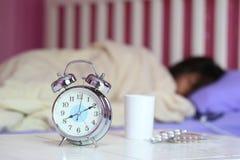Sveglia e bicchiere d'acqua, medicina con la donna che dorme dentro fotografia stock libera da diritti