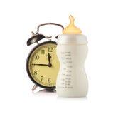 Sveglia e bottiglia di alimentazione del bambino con latte fotografia stock libera da diritti