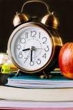 Sveglia e mela rossa sopra una pila di libri di esercizi, taccuini, cuscinetti Matite, penne, gomma sul desktop Lavagna nera Immagine Stock