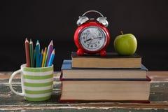 Sveglia e mela sulla pila di libri con il supporto della penna Fotografie Stock