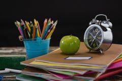 Sveglia e mela sulla pila di libri con il supporto della penna Fotografia Stock Libera da Diritti