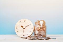 Sveglia e monete di legno su fondo bianco Immagini Stock