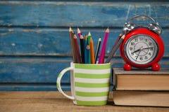 Sveglia, libri e supporto della penna Fotografia Stock
