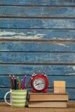 Sveglia, libri, fermacarte e supporto della penna Immagini Stock
