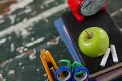 Sveglia, mela e gesso sulla pila di libri con il supporto della penna Fotografia Stock