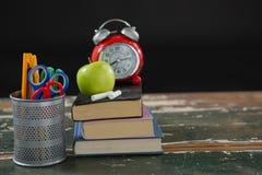 Sveglia, mela e gesso sulla pila di libri con il supporto della penna Immagini Stock