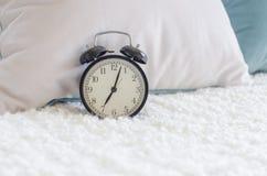 Sveglia nera moderna sul letto Fotografie Stock Libere da Diritti