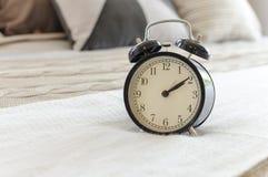 Sveglia nera moderna sul letto Immagini Stock