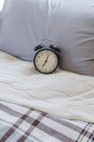 Sveglia nera moderna sul letto Fotografia Stock