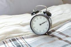 Sveglia nera moderna sul letto in camera da letto Fotografia Stock