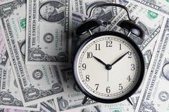 Sveglia nera sulle banconote del dollaro americano come tempo per soldi informati Fotografie Stock Libere da Diritti