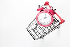Sveglia rosa nel carrello di compera su un fondo bianco Concetto - tempo di comprare Vista da sopra immagini stock