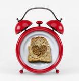 Sveglia rossa con il concetto del cuore del pane del pane tostato isolata su fondo bianco Fotografia Stock