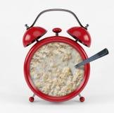 Sveglia rossa con il concetto del porridge isolata su fondo bianco Fotografia Stock