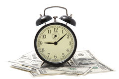 Sveglia sopra il mucchio di soldi isolato Fotografie Stock