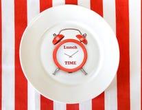 Sveglia sul piatto bianco Fondo di concetto di tempo del pranzo Fotografia Stock