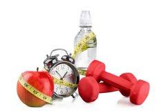 Sveglia verde, mela, bottiglia di acqua Fotografie Stock