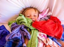 Sveglio, adorabile, sorridendo, ragazzo caucasico che risiede in un mucchio della lavanderia sporca sul letto immagini stock libere da diritti