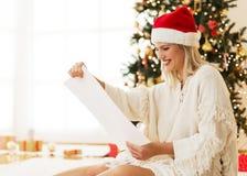 Sveglio, giovane donna con Santa& x27; lettura del cappello di s da una lista Fotografie Stock Libere da Diritti