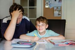 Sveglio poco ragazzo del bambino della scuola a casa che fa compito con il papà Piccolo scrittura con le matite variopinte, aiuto immagini stock