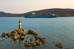 Svend Maersk container ship passes a small lighthouse at sunset. Nakhodka Bay. East (Japan) Sea. 19.04.2014 Stock Images
