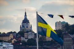 Svensk flagga som är främst av en av de mest härliga byggnaderna av Stockholm arkivbilder