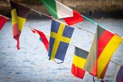 Svensk flagga under andra flaggor royaltyfri foto