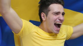 Svensk ung man som firar, medan rymma flaggan av Sverige i ultrarapid lager videofilmer