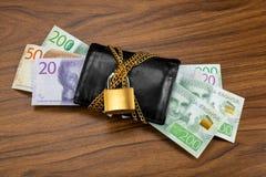 Svenska sedlar som ut klibbar från en låst svart plånbok Arkivfoton