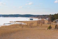 Svensken seglar utmed kusten i vinter med is och snöar Arkivfoton