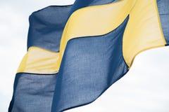 Svenskflagga i vinden royaltyfria bilder