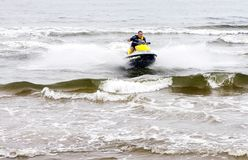 Young man performing tricks on jet ski on the sea waves. Sventoji, Lithuania - August 13, 2018: Young man riding on jet ski performing tricks on the sea waves at stock image