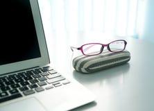 Svepa överkant- och läsningglassess på kontorsskrivbordet med fönster baktill royaltyfri fotografi