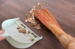Svepande pengar i en skopa med en kvast Royaltyfri Fotografi