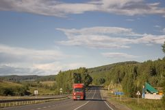 Sverdlovsk region, Ural, Russia. September 1, 2017. Asphalt road with cars on it going across mountains and green forests. Trees a. Nd their shadows on the grass Royalty Free Stock Photo
