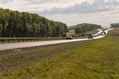 Sverdlovsk region, Ural, Russia. September 1, 2017. Asphalt road with cars on it going across mountains and green forests. Trees a. Nd their shadows on the grass Royalty Free Stock Photos