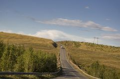 Sverdlovsk region, Ural, Russia. September 1, 2017. Asphalt road with cars on it going across mountains and green forests. Trees a. Nd their shadows on the grass Royalty Free Stock Image