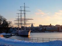 Sverige - vinter Stockholm - seglingskepp nära kaj på solnedgången Arkivfoto