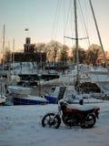 Sverige - vinter Stockholm - yachter och cykel i snö på solnedgången Arkivfoto