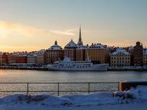 Sverige - vinterStockholm sikt till Gamlastan från vatten - enkelt skepp nära kaj på solnedgången Arkivfoton