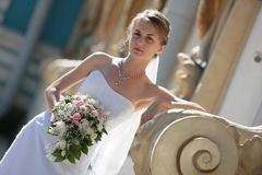 Sveta and buch. The bride in a white dress with a bunch of flowers in park Stock Images