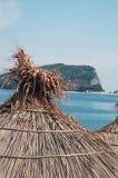 Sveti Nikola island. Scenic view of Sveti Nikola island with straw beach umbrella or parasol in foreground, Budva Riviera, Montenegro Stock Photos