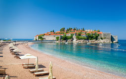 Sveti Stefan luxury sand beach with chaise-longue chairs and umbrellas. Luxury sand beach with wooden chaise-longue chairs and umbrellas near the Sveti Stefan royalty free stock images
