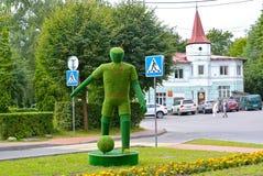 Svetlogorsk,俄罗斯 以大厦为背景的Topiarny雕塑足球运动员 免版税库存照片
