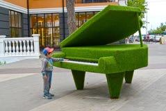 Svetlogorsk,俄罗斯 小男孩在一架topiarny雕塑大平台钢琴附近站立 免版税库存图片