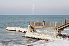 SVETLOGORSK, RÉGION DE KALININGRAD, RUSSIE - 27 FÉVRIER 2011 : Touristes sur une longue jetée regardant la mer baltique Images stock