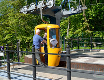 SVETLOGORSK, RUSSIA. The worker of a ropeway helps the female passenger to leave a cabin Stock Images