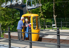SVETLOGORSK, RUSSIA.The worker of a ropeway helps the passenger to leave a cabin Royalty Free Stock Image